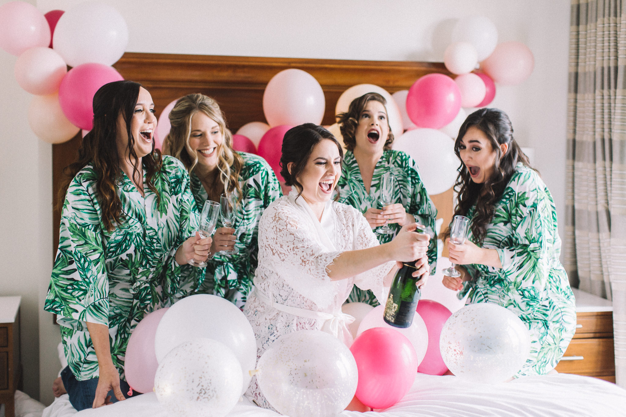 bridesmaids pop champagne on bed photo