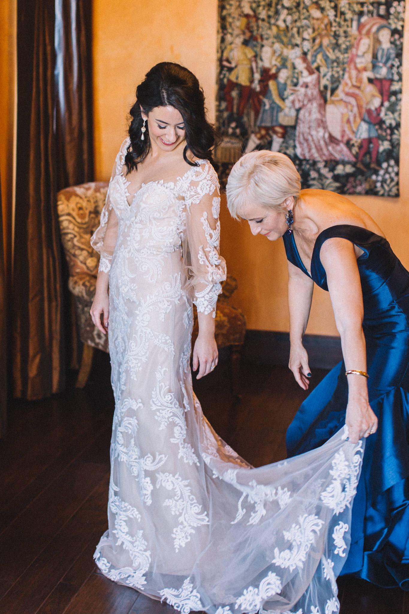 bride with mom putting on wedding dress